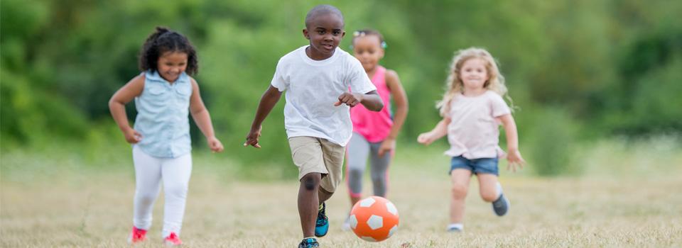 photo of kids running after a ball