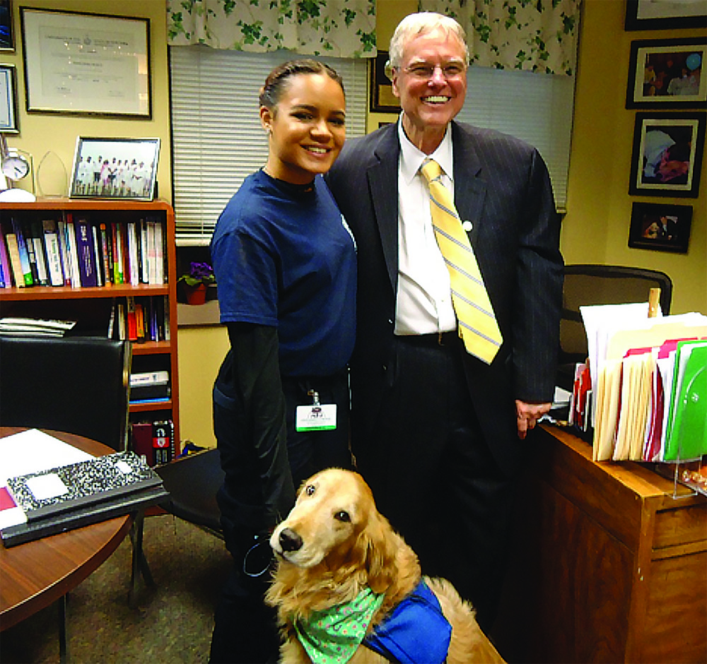 Photo of Dr Crenshaw with facility service dog and trainer