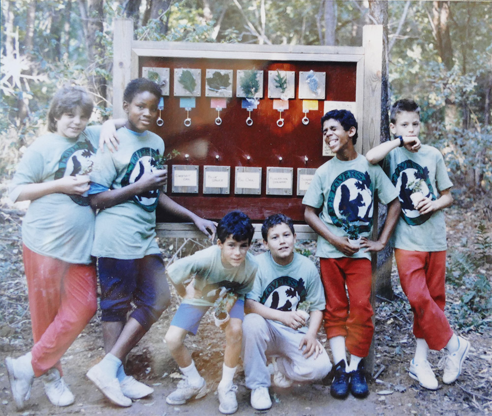 group of boys posing in front a nature board in the woods