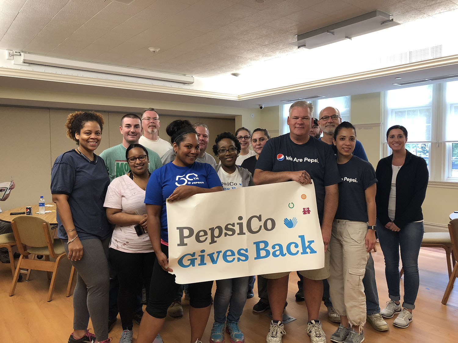 photo of Pepsico volunteers holding sign that says PepsiCo Gives Back