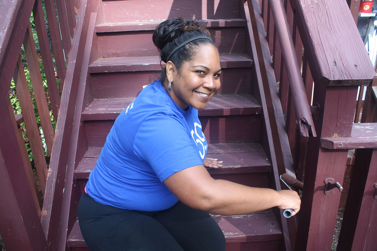 photo of smiling volunteer painting a stair railing