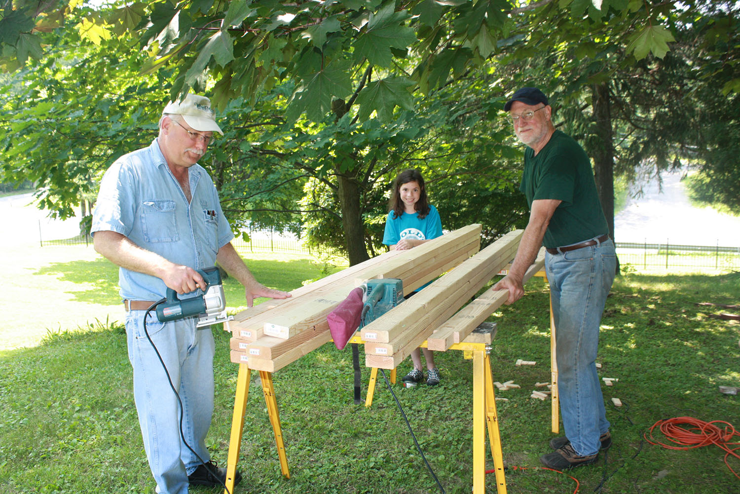 Volunteers cutting two by fours