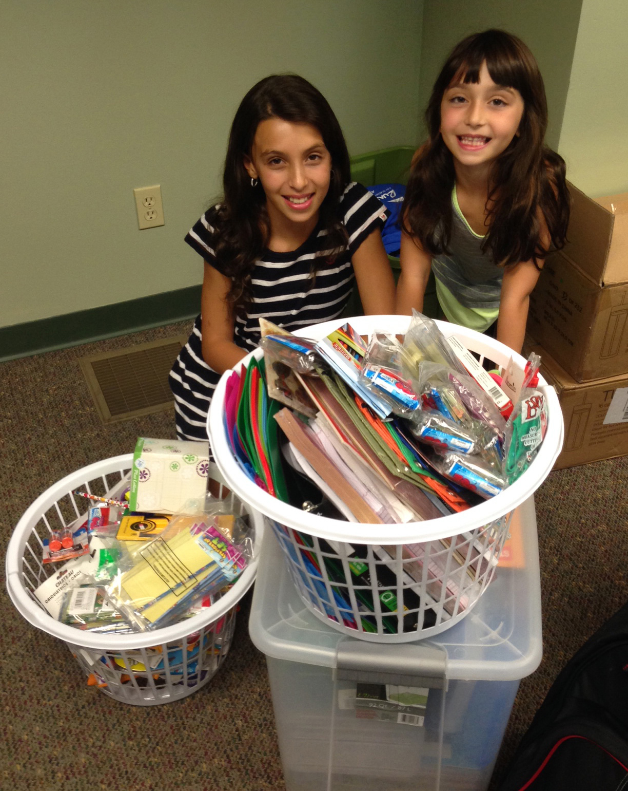 photo of two young girls with baskets of donated school supplies